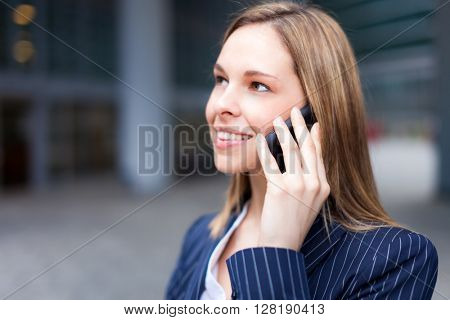 Portrait of a young smiling business woman talking on her mobile phone in a business environment