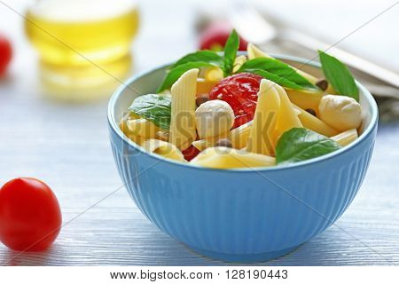 Cooked penne pasta with mozzarella, fresh tomatoes and basil in blue bowl on wooden table
