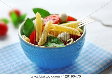 Cooked penne pasta with mozzarella, fresh tomatoes and basil in blue bowl