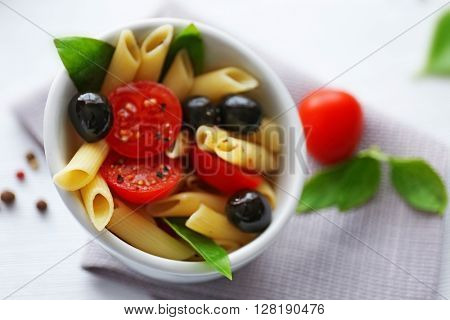 Cooked penne pasta with olives, fresh tomatoes and basil in white bowl