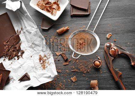 Pieces of chocolate with kitchen tools on black wooden table