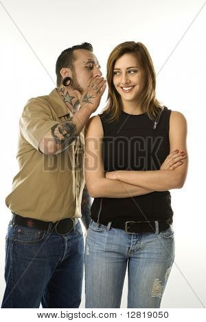 Caucasian mid-adult man whispering into ear of teen female.