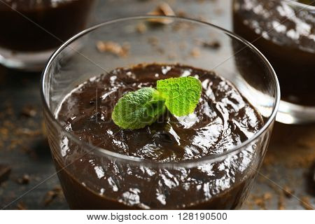 Glass cup of chocolate dessert with fresh mint on black wooden table, close up