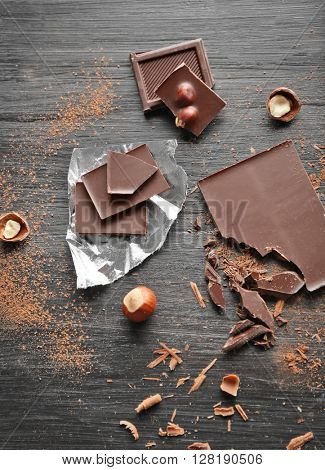 Pieces of chocolate with hazelnuts on black wooden background