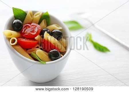 Cooked penne pasta with olives, fresh tomatoes and basil in white bowl on wooden table