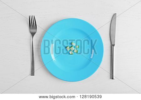 Pieces of cucumber in a blue plate on white table.. Top view.