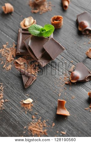 Pieces of chocolate with hazelnuts and fresh mint on black wooden background