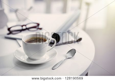 White cup of the coffee on wooden table  in a light room..
