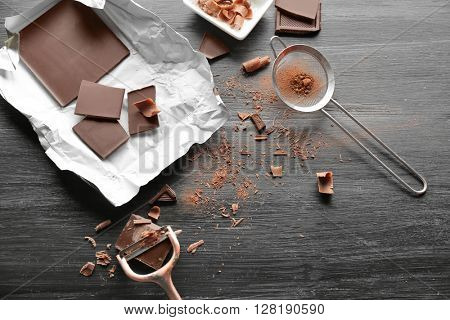 Pieces of chocolate with strainer and peeler on black wooden background