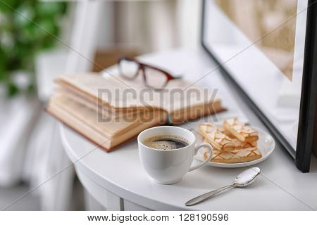 White cup of the coffee on the table  in a light room..