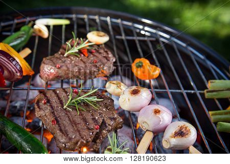 Assorted delicious beef steaks with vegetable on a barbecue grill.