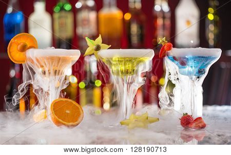 Cocktails with ice vapor on bar desk, close-up.