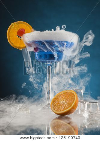 Cocktail with ice vapor on bar desk, close-up.