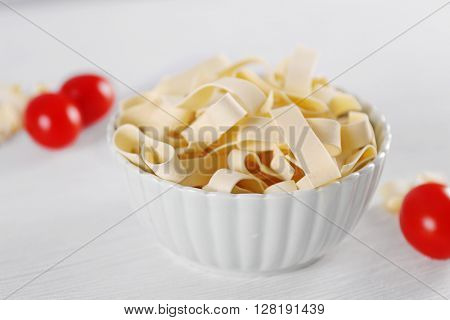 Bowl of uncooked pasta on wooden background