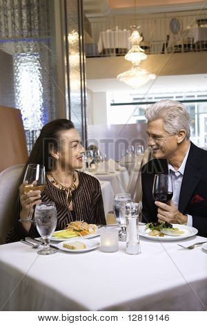 Caucasian mature adult male and prime adult female sitting at restaurant table.