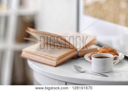 White cup of the coffee on the table  in a light room.