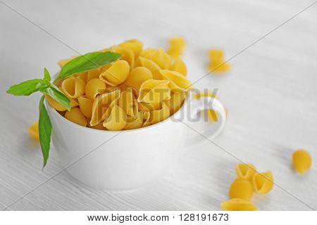 Fresh uncooked pasta in bowl on wooden table closeup