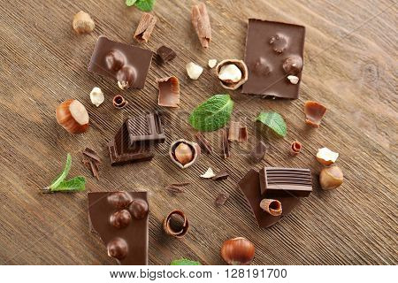 Broken black chocolate with hazelnuts and fresh mint on wooden table