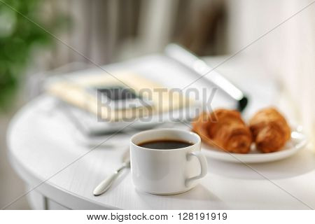 White cup of the coffee and a phone on the table  in a light room.