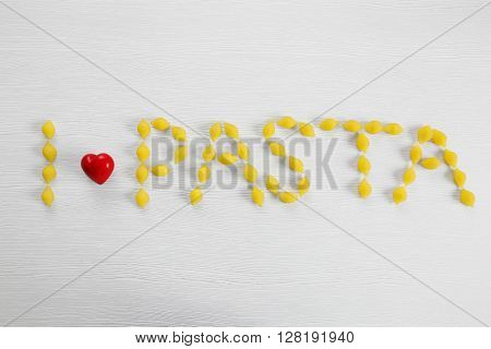 Phrase I LOVE PASTA from fresh uncooked pasta on wooden background