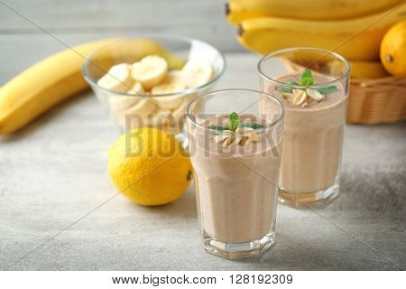 Fresh banana cocktail with peanuts on grey background