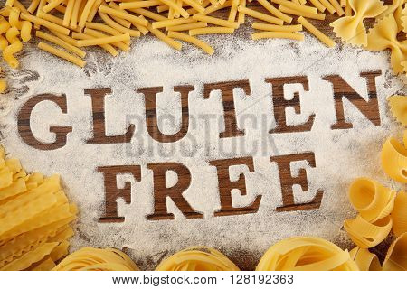 Text GLUTEN FREE with flour and pasta on wooden surface, top view