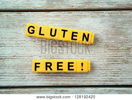 Phrase GLUTEN FREE made of yellow cubes on wooden background