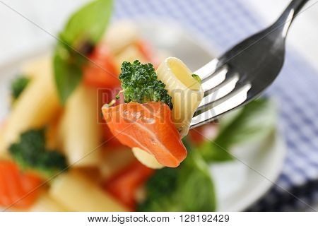 Plate of pasta with salmon and broccoli closeup