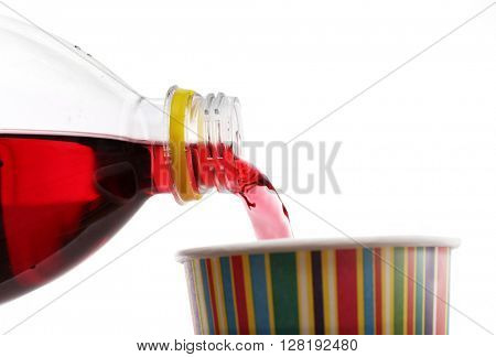 Pouring cherry soda from plastic bottle into cup on grey background