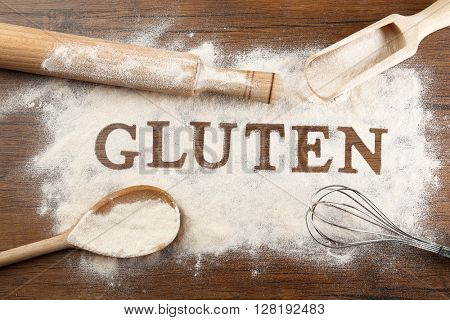 The word GLUTEN from flour on wooden table, top view