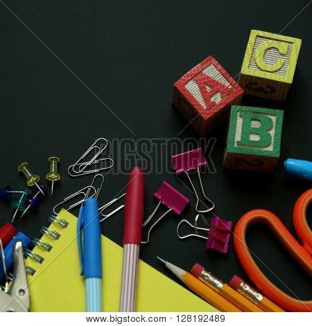 School supplies on a black chalkboard