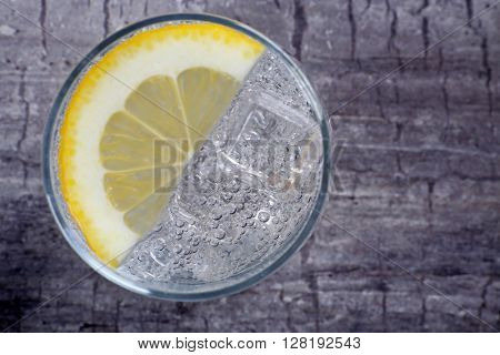 Glass of soda with ice and lemon on rustic wooden background