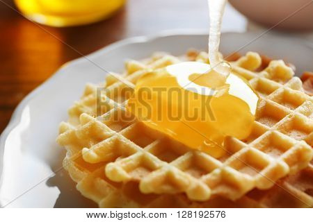 Waffles with honey on wooden background