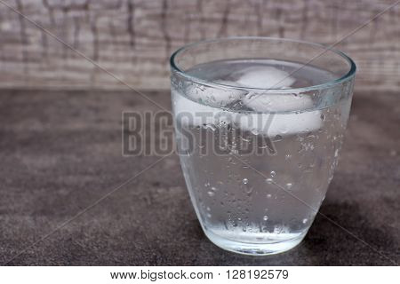 Glass of soda with ice on grey background