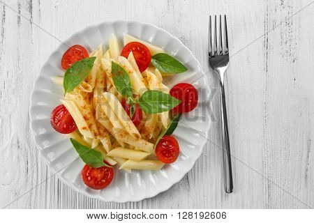 Plate of pasta with cherry tomatoes and basil leaves on wooden table, top view