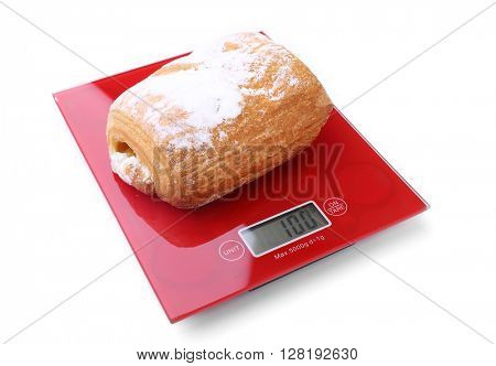 Puff bun on digital kitchen scales, isolated on white
