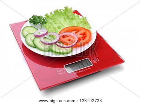 Plate with sliced fresh vegetables on digital kitchen scales, isolated on white