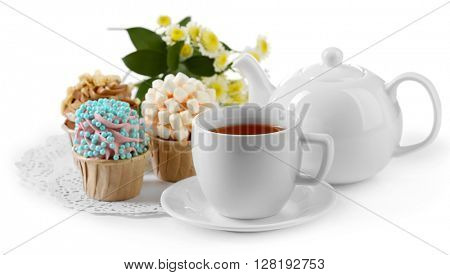 Cup of tea with tasty cupcakes and teapot, isolated on white