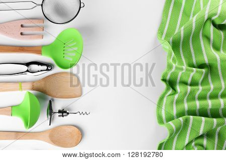 Set of stainless and wooden utensils with towel, isolated on white