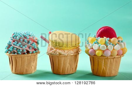 Tasty cupcakes with macaroon on turquoise background