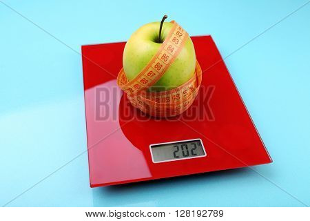 Apple with centimeter on digital kitchen scales on blue background