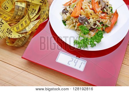 Plate with pilaf on digital kitchen scales and centimeter over wooden background