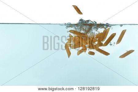 Penne pasta falling in water