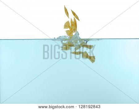 Farfalle pasta falling in water