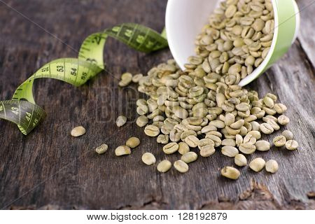 Green coffee beans in a cup with measuring tape on wooden table