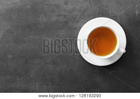 Cup of tea on grey background, top view