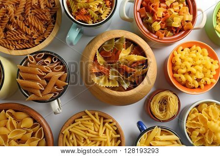 Various types of pasta in dishes, top view