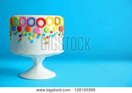 Birthday cake with colorful decorations on blue background.