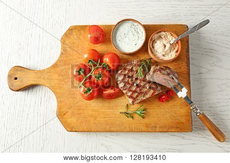 Delicious grilled steak on cutting board