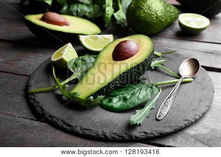 Sliced avocado with lime, spinach and arugula on slate plate